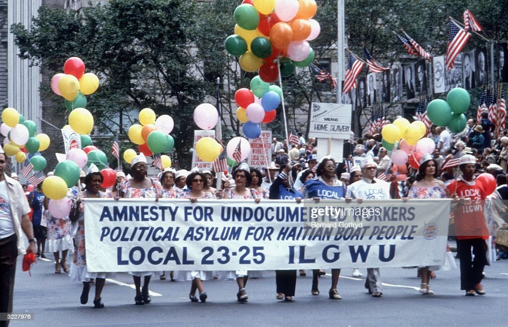 Members of the International Ladies' Garment Workers Union march in the New York City Labor Day Parade, carrying a banner calling for worker's rights and political asylum for Haitian boat people. The crowd carries balloons in the background.