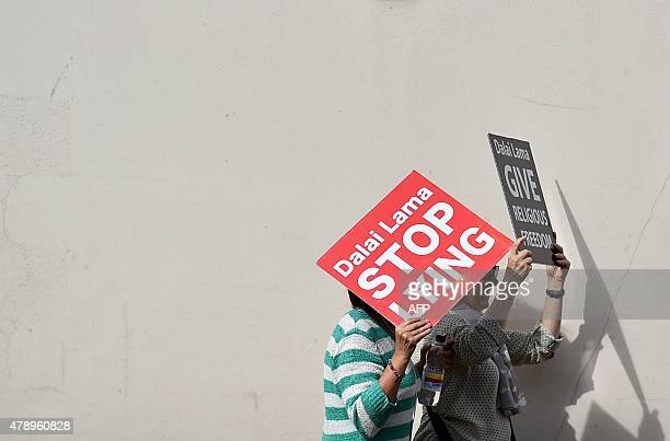 Members of the International Shugden Community protest outside of Aldershot football club ahead of the arrival of the Dalai Lama on June 29 2015 The...