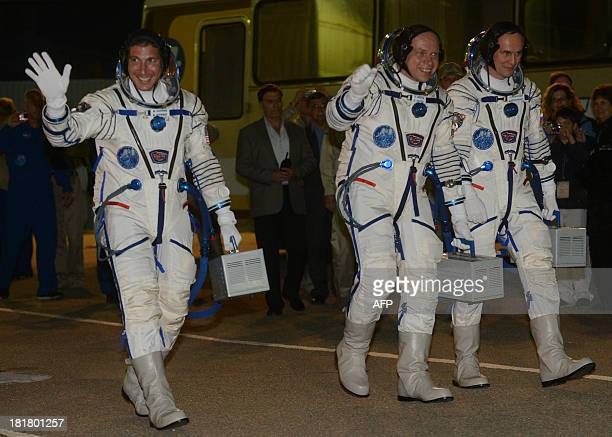 Members of the International space crew US astronaut Michael Hopkins Russia's cosmonauts Oleg Kotov and Sergey Ryazansky walk to a their bus after...