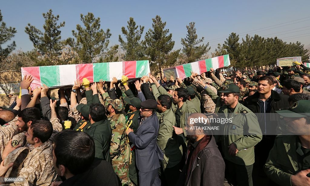 Members of the Iranian Revolutionary Guard carry the caskets of Iran's Revolutionary Guards Brigadier General Mohsen Ghajarian and other Iranian 'volunteers', who were reportedly killed in the northern province of Aleppo in the fight against the Islamic State (IS) jihadist group, during their funeral procession in the capital Tehran, on February 6, 2016. Brigadier General Mohsen Ghajarian of the elite Revolutionary Guards was killed in the northern province of Aleppo, according to the Fars news agency, which is close to the Guards. He was advising pro-government forces in the fight against the Islamic State (IS) jihadist group, it reported, without saying when he died. KENARE
