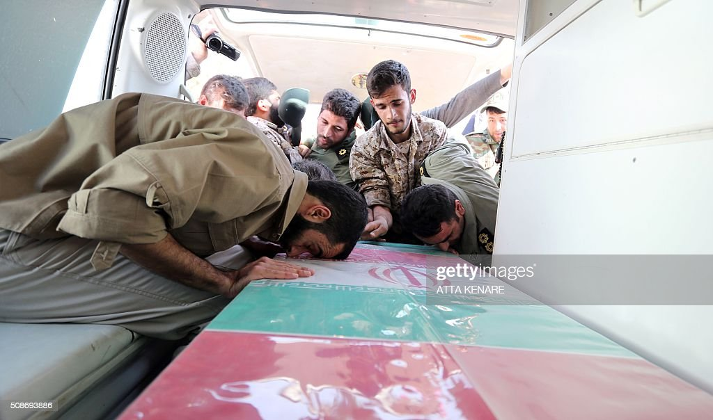 Members of the Iranian Revolutionary Guard mourn over the casket of Iran's Revolutionary Guards Brigadier General Mohsen Ghajarian, who was reportedly killed in the northern province of Aleppo in the fight against the Islamic State (IS) jihadist group, during his funeral procession in the capital Tehran, on February 6, 2016. Brigadier General Mohsen Ghajarian of the elite Revolutionary Guards was killed in the northern province of Aleppo, according to the Fars news agency, which is close to the Guards. He was advising pro-government forces in the fight against the Islamic State (IS) jihadist group, it reported, without saying when he died. KENARE