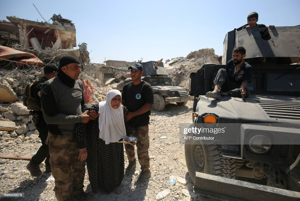 TOPSHOT - Members of the Iraqi anti-terrorism forces (CTS) help an elderly woman as they advance through the Old City of Mosul on June 21, 2017, during the ongoing offensive to retake the last district still held by the Islamic State (IS) group. /