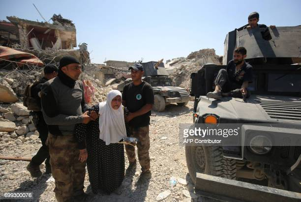 TOPSHOT Members of the Iraqi antiterrorism forces help an elderly woman as they advance through the Old City of Mosul on June 21 during the ongoing...