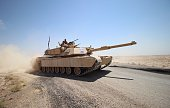 Members of the Iraqi army flash the sign for victory as they maneuver a tank on the front line during a military operation against Islamic State...
