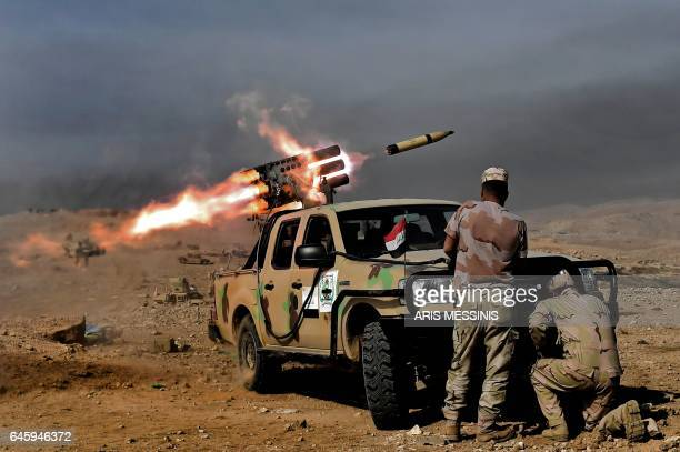 TOPSHOT Members of the Iraqi army's 9th Division fire a multiple rocket launcher from a hill in Talul alAtshana on the southwestern outskirts of...
