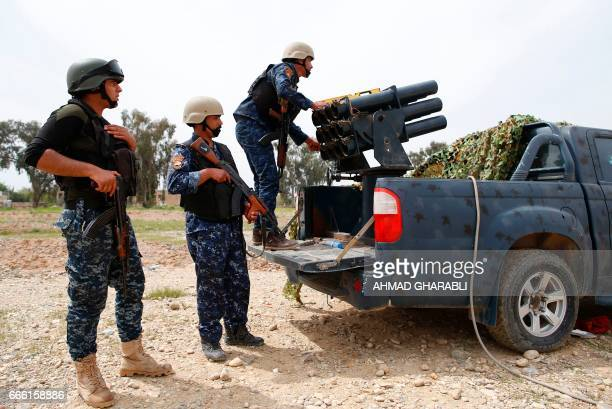 Members of the Iraqi army's 9th Division prepare to fire a multiple rocket launcher at a position in western Mosul on April 8 during a military...