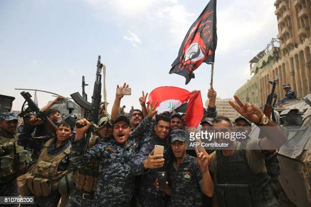 TOPSHOT Members of the Iraqi federal police dance and wave their country's national flag in celebration in the Old City of Mosul on July 8 as their...