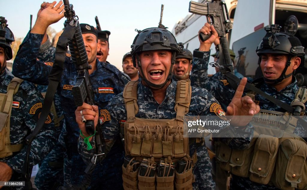 Members of the Iraqi federal police forces celebrate in the Old City of Mosul on July 10, 2017 after the government's announcement of the 'liberation' of the embattled city from Islamic State (IS) group fighters. Iraqi Prime Minister Haider al-Abadi's office said he was in 'liberated' Mosul to congratulate 'the heroic fighters and the Iraqi people on the achievement of the major victory'. / AFP PHOTO / Fadel SENNA