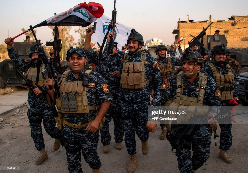 TOPSHOT - Members of the Iraqi federal police forces celebrate in the Old City of Mosul on July 10, 2017 after the government's announcement of the 'liberation' of the embattled city from Islamic State (IS) group fighters. Iraqi Prime Minister Haider al-Abadi's office said he was in 'liberated' Mosul to congratulate 'the heroic fighters and the Iraqi people on the achievement of the major victory'. / AFP PHOTO / Fadel SENNA