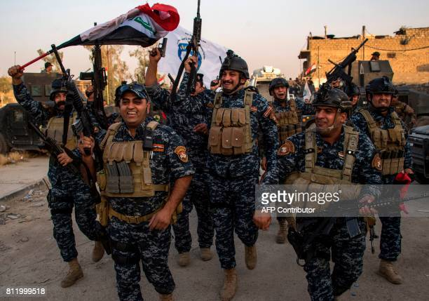 TOPSHOT Members of the Iraqi federal police forces celebrate in the Old City of Mosul on July 10 2017 after the government's announcement of the...