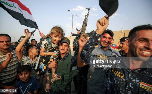TOPSHOT Members of the Iraqi federal police pose for a picture with children during a celebration in the Old City of Mosul where the gruelling battle...
