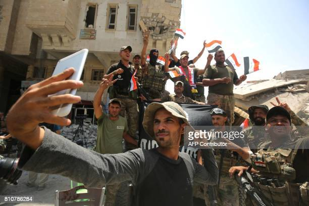 Members of the Iraqi federal police take a selfie in celebration in the Old City of Mosul on July 8 as their part of the battle has been declared...