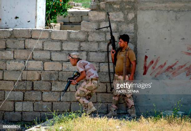 Members of the Iraqi forces advance in the northwestern alHaramat neighbourhood of Mosul on May 9 during the ongoing offensive to retake the area...