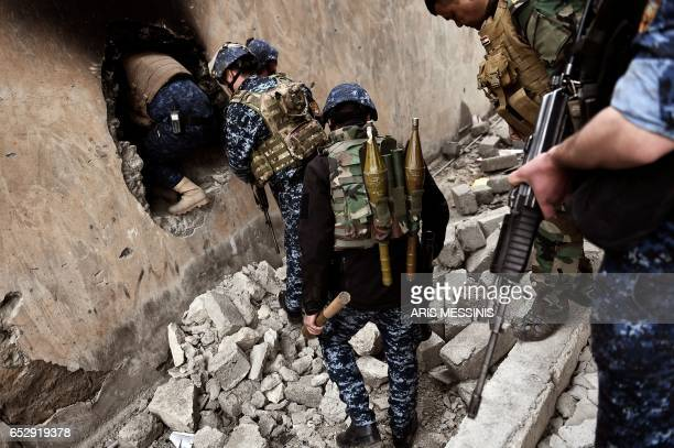 TOPSHOT Members of the Iraqi forces advance towards the Old City in western Mosul on March 13 during an offensive to retake the city from Islamic...