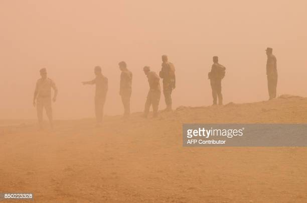 Members of the Iraqi forces backed by paramilitary units advance in an area south of Anna in the vast western province of Anbar bordering Syria on...