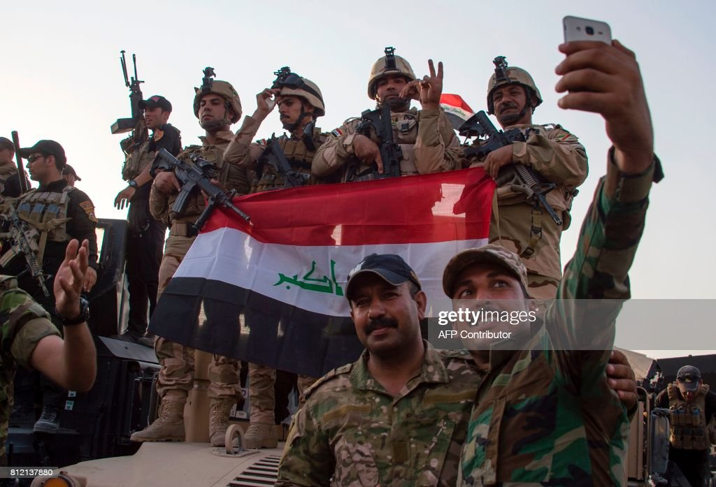 TOPSHOT - Members of the Iraqi forces celebrate in the Old City of Mosul on July 10, 2017 after the government's announcement of the 'liberation' of the embattled city from Islamic State (IS) group fighters. Iraqi Prime Minister Haider al-Abadi's office said he was in 'liberated' Mosul to congratulate 'the heroic fighters and the Iraqi people on the achievement of the major victory. /