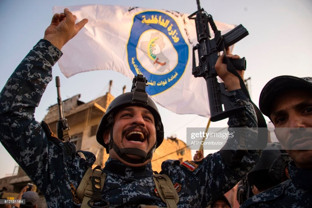 TOPSHOT - Members of the Iraqi forces celebrate in the Old City of Mosul on July 10, 2017 after the government's announcement of the 'liberation' of the embattled city from Islamic State (IS) group fighters. Iraqi Prime Minister Haider al-Abadi's office said he was in 'liberated' Mosul to congratulate 'the heroic fighters and the Iraqi people on the achievement of the major victory.' /
