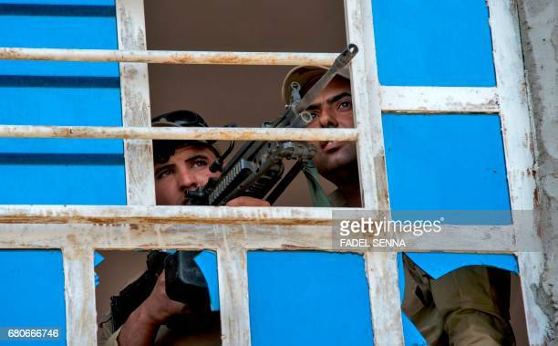 TOPSHOT Members of the Iraqi forces guard a position in the northwestern alHaramat neighbourhood of Mosul on May 9 during the ongoing offensive to...