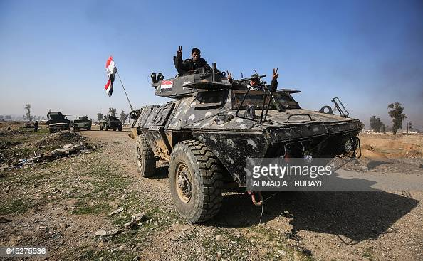 TOPSHOT Members of the Iraqi forces raise the victory gesture from an armoured vehicle during their advance towards Dindan neighborhood in the...