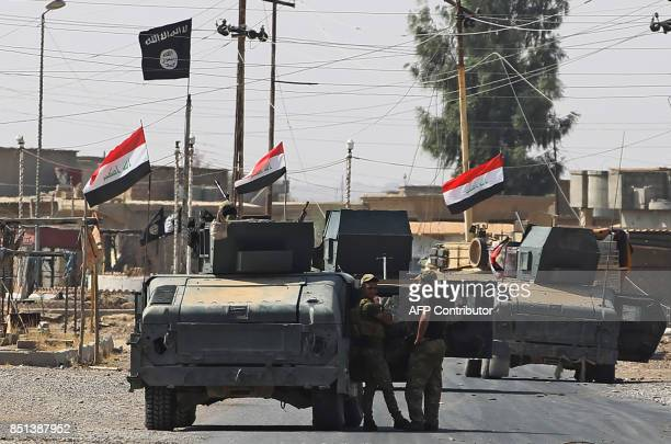 Members of the Iraqi forces rest outside a humvee in the northern Iraqi town of Sharqat on September 22 with an Islamic State group flag seen flying...
