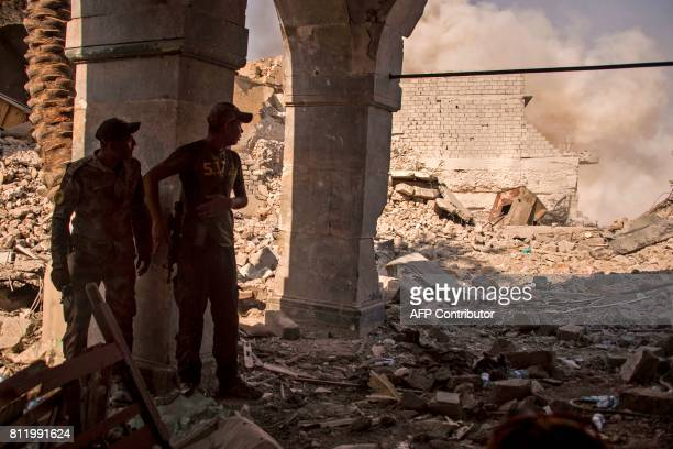 Members of the Iraqi forces stand behind a pillar as smoke plumes billow in the background during the offensive against Islamic State group fighters...