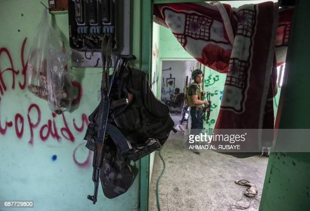 TOPSHOT Members of the Iraqi forces stand guard in a house on the frontline in the old city of Mosul on May 24 during the ongoing offensive to retake...