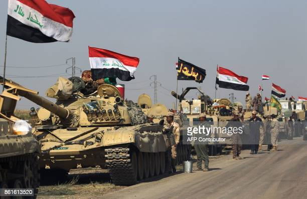 Members of the Iraqi forces stand next to a convoy heading to Kurdish peshmerga positions on October 15 on the southern outskirts of Kirkuk The...