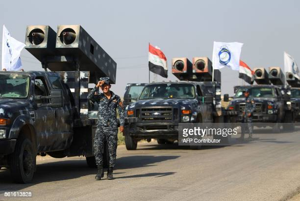 Members of the Iraqi forces stand next to vehicles mounted with rocket launchers and heading to Kurdish peshmerga positions on October 15 on the...