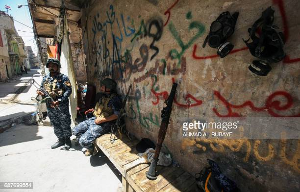 TOPSHOT Members of the Iraqi forces take a break near the frontline in the old city of Mosul on May 24 during the ongoing offensive to retake the...