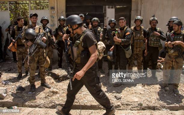 Members of the Iraqi forces take position in a neighbourhood of west Mosul on May 17 during an ongoing offensive to retake the area from Islamic...