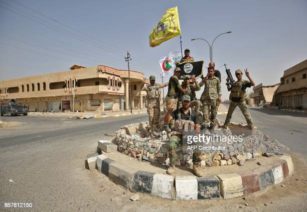 TOPSHOT Members of the Iraqi forces which are backed by fighters from the Hashed alShaabi pose for a photograph in Hawija on October 5 after retaking...