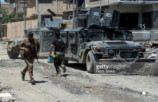 Members of the Iraqi forces with armoured fighting vehicles take position in Mosul's western Rifai neighbourhood on May 17 during an ongoing...