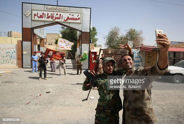 Members of the Iraqi government forces take a selfie in front of a hospital as they celebrate in the town of Sharqat around 80 kilometres south of...