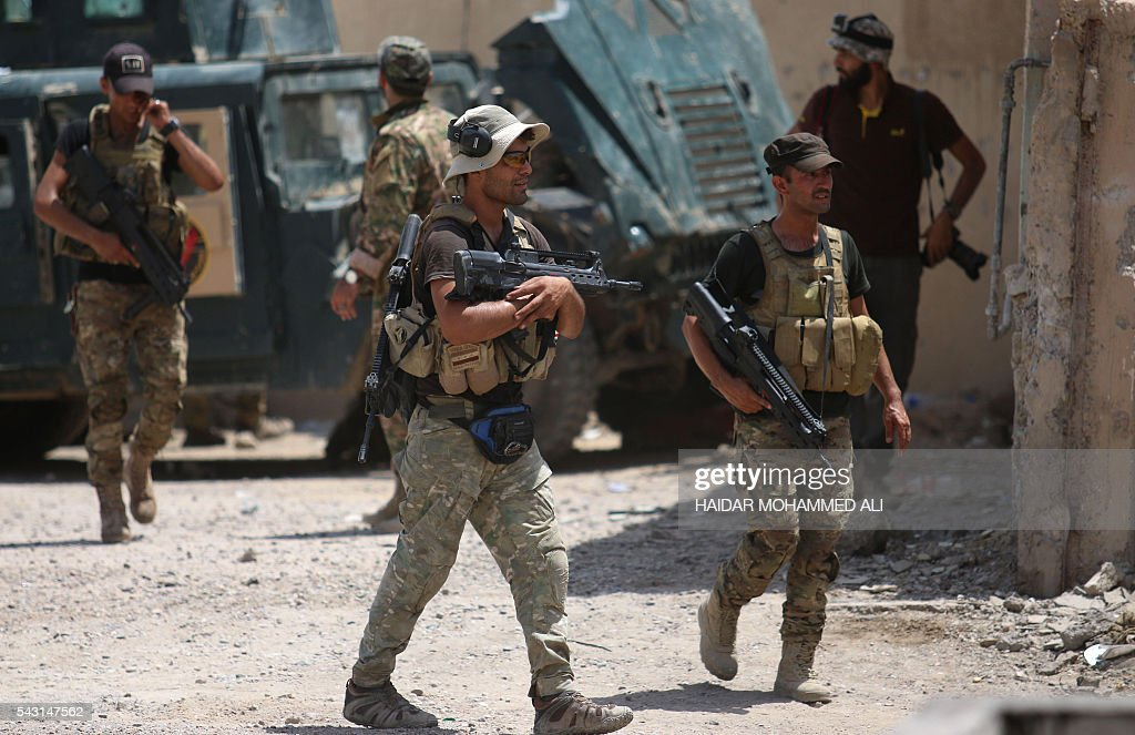 Members of the Iraqi government forces walk in Fallujah, 50 kilometres (30 miles) from the capital Baghdad, after forces retook the embattled city from the Islamic State group on June 26, 2016. Iraqi Prime Minister Haider al-Abadi urged all Iraqis to celebrate the recapture of Fallujah by the security forces and vowed the national flag would be raised in Mosul soon. While the battle has been won, Iraq still faces a major humanitarian crisis in its aftermath, with tens of thousands of people who fled the fighting desperately in need of assistance in the searing summer heat. ALI