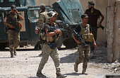 Members of the Iraqi government forces walk in Fallujah 50 kilometres from the capital Baghdad after forces retook the embattled city from the...