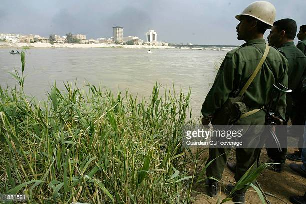 Members of the Iraqi militia search the river and set fire to reeds March 23 2003 in Baghdad Iraq They are searching for two coalition pilots...