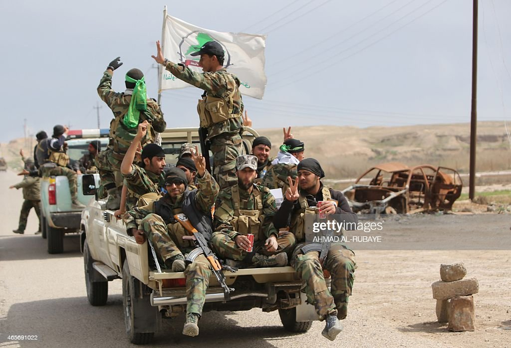 Members of the Iraqi paramilitary Popular Mobilisation units which are dominated by Shiite militias flash the 'V' for victory sign after regaining...