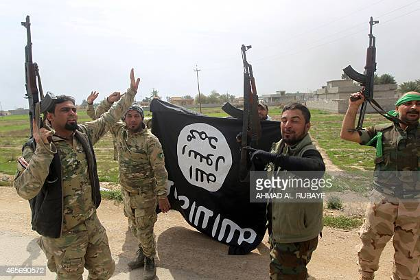 Members of the Iraqi paramilitary Popular Mobilisation units celebrate with a flag of the Islamic State group after retaking the village of Albu Ajil...