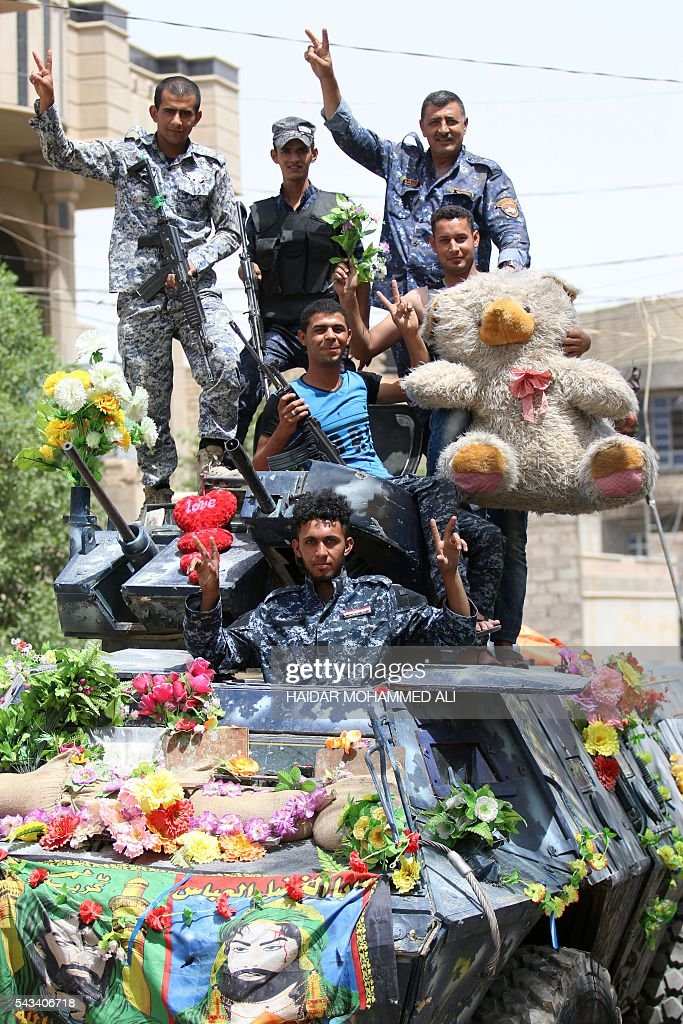 Members of the Iraqi police forces pose with a teddy bear on June 28, 2016, as they stand on what they say was the first armoured vehicle to enter Fallujah after retaking the city from the Islamic State group. Iraqi forces took the Islamic State group's last positions in Fallujah on June 26, 2016, establishing full control over one of the jihadists' most emblematic bastions after a month-long operation. / AFP / HAIDAR