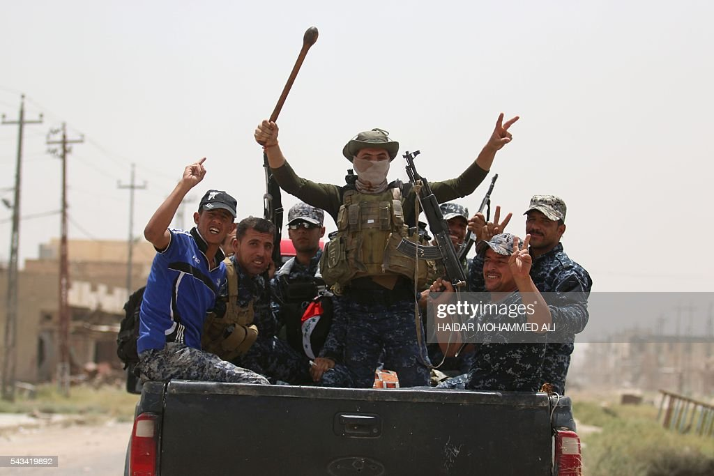 Members of the Iraqi police forces raise weapons and flash the V-sign for 'victory' as they patrol a street in Fallujah on June 28, 2016, after Iraqi forces retook the city from the Islamic State group. Iraqi forces took the Islamic State group's last positions in Fallujah on June 26, 2016, establishing full control over one of the jihadists' most emblematic bastions after a month-long operation. / AFP / HAIDAR