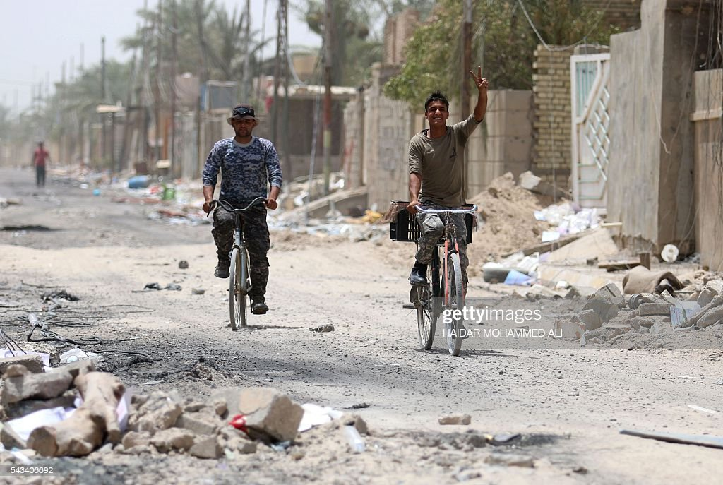 Members of the Iraqi police forces ride bicycles on a damaged street in Fallujah on June 28, 2016, after Iraqi forces retook the city from the Islamic State group. Iraqi forces took the Islamic State group's last positions in Fallujah on June 26, 2016, establishing full control over one of the jihadists' most emblematic bastions after a month-long operation. / AFP / HAIDAR