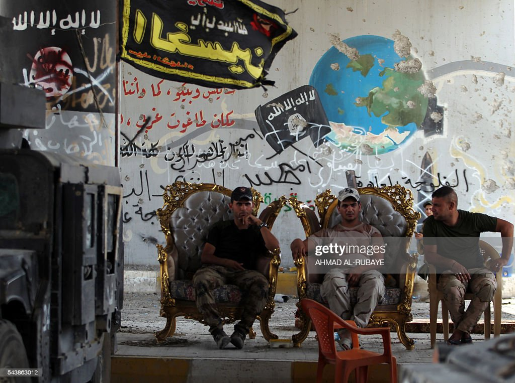 Members of the Iraqi police forces sit outside a building in the city of Fallujah on June 30, 2016 after they've recaptured the city from Islamic State (IS) group jihadists. Iraqi forces have retaken full control of Fallujah, a longtime jihadist bastion just 50 kilometres (30 miles) west of Baghdad, after a vast operation that was launched in May. / AFP / AHMAD