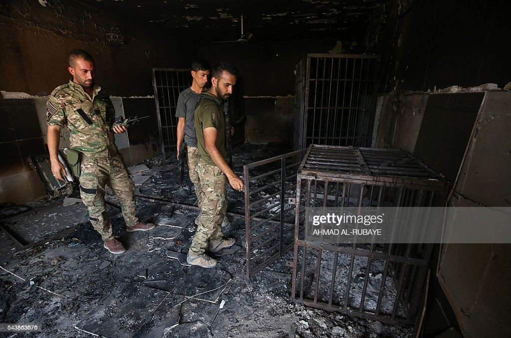 Members of the Iraqi police inspect a prison previously used by Islamic State (IS) group jihadists in the city of Fallujah on June 30, 2016 after the city was recaptured by government forces. Iraqi forces have retaken full control of Fallujah, a longtime jihadist bastion just 50 kilometres (30 miles) west of Baghdad, after a vast operation that was launched in May. / AFP / AHMAD