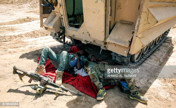 TOPSHOT Members of the Iraqi progovernment Hashed alShaabi paramilitary forces take a break as forces advance towards the UNESCOlisted ancient city...