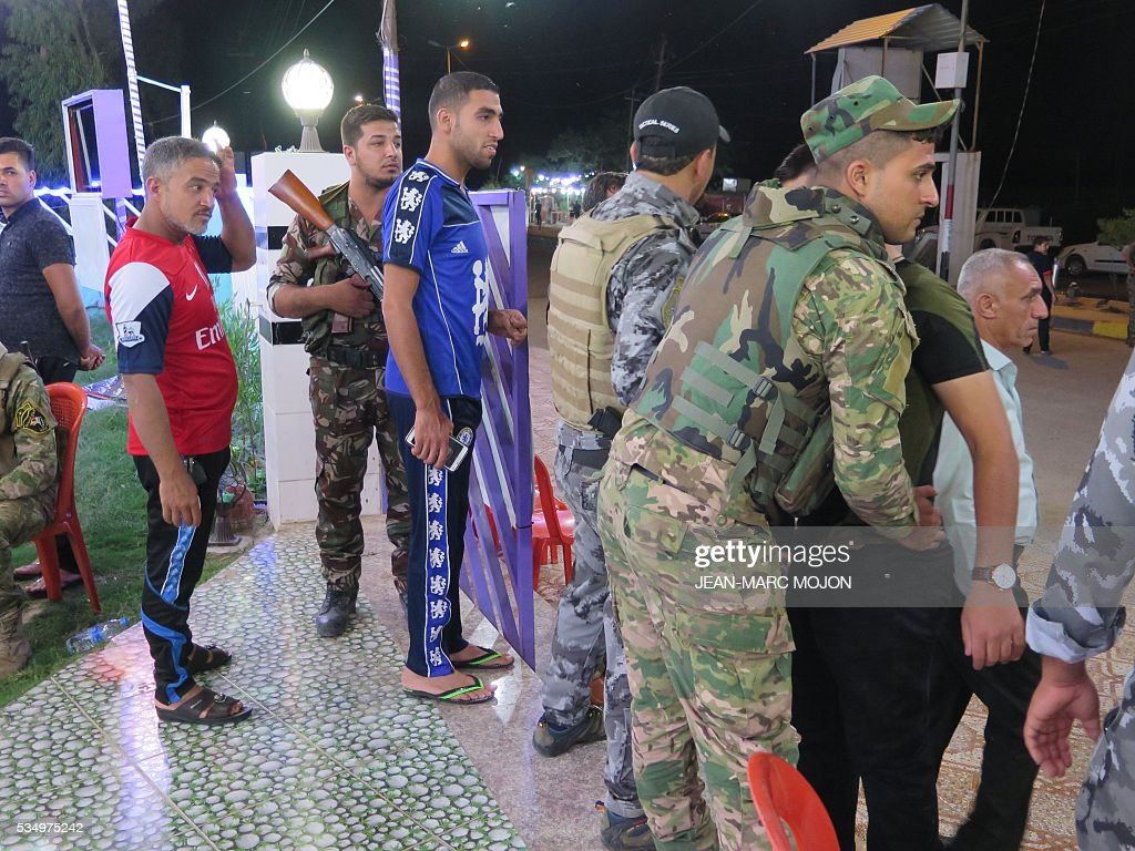 Members of the Iraqi security forces frisk young men during a memorial ceremony at the Al-Furat cafe in Balad, 80 km north of Baghdad, ahead of the Champions League final between Real Madrid and Atletico Madrid. The cafe, which hosts a local Real Madrid fan club, was the scene on May 13 of an attack that left a total of 16 people dead, according to officials. The deadly was claimed by the Islamic State group and sparked an outpouring of sympathy from the football world. / AFP / Jean-Marc Mojon