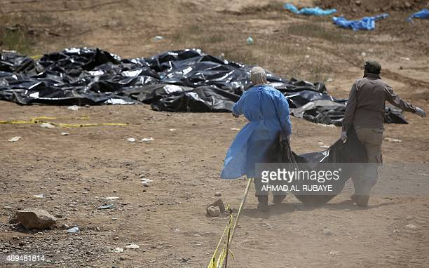 Members of the Iraqi security forces work at the site of a mass grave containing the remains of people believed to have been slain by jihadists of...
