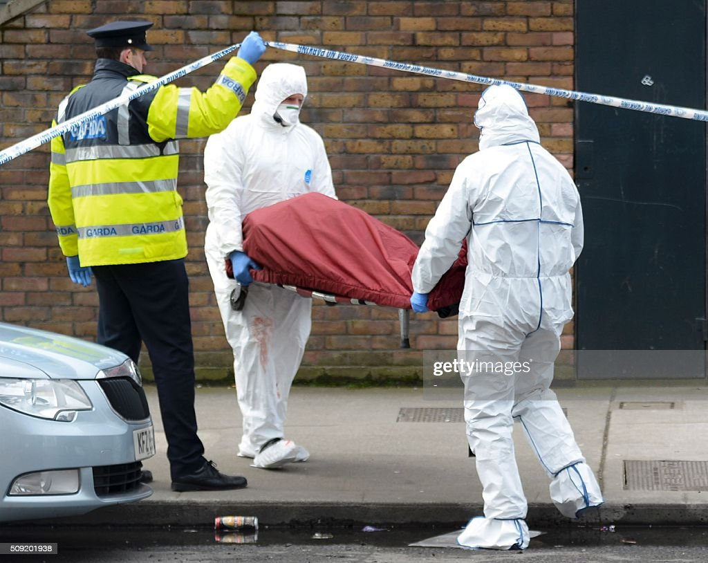 Members of the Irish emergency services carry a gurney taken from a residential address that was the scene of a fatal shooting and put it into an ambulance in Dublin on February 9, 2016. A man was shot dead in Dublin on February 8, Irish police said, in a suspected gangland reprisal attack for a fatal shooting at a boxing event last week. The victim was named by Ireland's national broadcaster RTE as Eddie Hutch, brother of the north Dublin crime figure known as 'The Monk' and the uncle of Irish criminal Gary Hutch, whose 2015 killing in Spain is thought to have begun the feud. / AFP / -