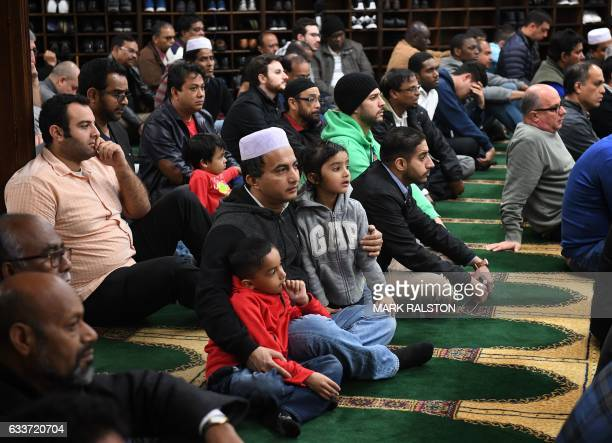Members of the Islamic community listen during a prayer session and solidarity rally held in conjunction with interfaith religious leaders as they...