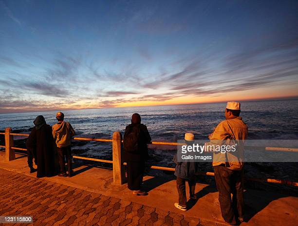 Members of the Islamic community look out to sea from the Sea Point beach front during the sighting of the new moon which marks the end of the month...