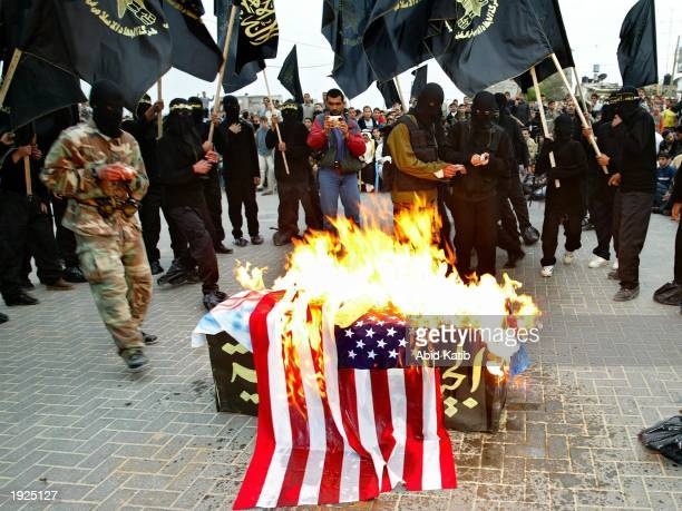 Members of the Islamic militant group Jihad burn US Israeli and British flags over a mock coffin symbolic of Arab armies during an antiAmerican...